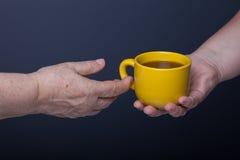 Mãos das pessoas idosas e das jovens mulheres no fundo preto Imagem de Stock