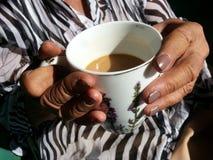 mãos das senhoras idosas que guardam uma xícara de café Fotografia de Stock Royalty Free