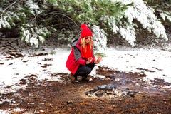 Mãos de agachamento e de aquecimento da menina da geada da mordida no fogo smouldering fotografia de stock royalty free