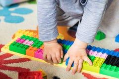 Mãos de 3 anos de jogo velho do menino com lego Imagem de Stock