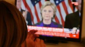 Mãos de aplauso da mulher que olham a tevê após as eleições dos E.U. que escutam o discurso de Hillary Clinton filme