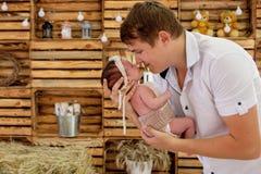 Mãos de apoio Gene guardar o seu bebê idoso de 14 dias em seus braços fotos de stock royalty free