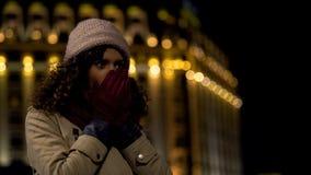 Mãos de aquecimento congeladas da senhora e ônibus de espera, iluminação bonita da cidade da noite imagem de stock royalty free
