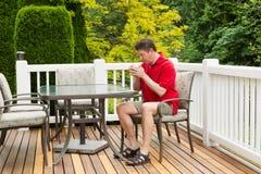 Mãos de aquecimento do homem maduro com café quente na caneca Fotos de Stock
