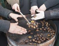 Mãos de aquecimento em castanhas quentes Foto de Stock Royalty Free