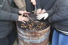 Mãos de aquecimento em castanhas quentes Imagens de Stock