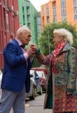 Mãos de beijo do ancião de uma mulher adulta Fotografia de Stock Royalty Free