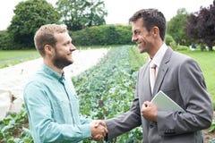 Mãos de And Businessman Shaking do fazendeiro imagens de stock
