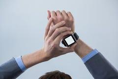 Mãos de Businessmans que verificam seu relógio esperto foto de stock royalty free