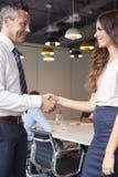 Mãos de And Businesswoman Shaking do homem de negócios na sala de reuniões moderna com os colegas que encontram-se em torno da ta foto de stock