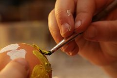 Mãos de cinco anos de menina idosa que pinta o coração amarelo no ovo da páscoa blowed com escova fina Fotografia de Stock Royalty Free