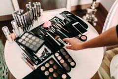 Mãos de cosméticos e de escovas de Many do maquilhador em uma tabela no salão de beleza Maquilhador do local de trabalho Imagem de Stock