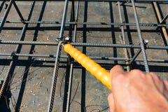 Mãos de fios do trabalhador do construtor para as hastes de metal de confecção de malhas foto de stock royalty free