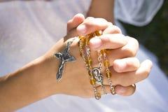 Mãos de grânulos e de cruz do rosário da terra arrendada da criança Foto de Stock Royalty Free
