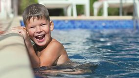 Mãos de inclinação de sorriso felizes do rapaz pequeno à borda da piscina que aprecia e que tem o movimento lento do divertimento vídeos de arquivo