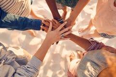 Mãos de jovens na pilha na praia imagens de stock