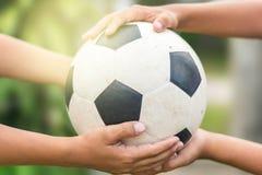 Mãos de Kid's que guardam o futebol velho foto de stock
