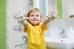 Mãos de lavagem da criança e mostrar as palmas ensaboadas Foto de Stock