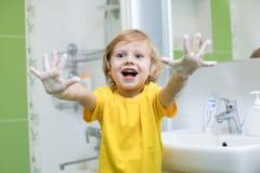 Mãos de lavagem da criança e mostrar as palmas ensaboadas Imagens de Stock