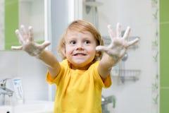 Mãos de lavagem da criança e mostrar as palmas ensaboadas Imagens de Stock Royalty Free