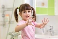 Mãos de lavagem da criança e mostrar as palmas ensaboadas Fotografia de Stock