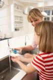 Mãos de lavagem da matriz e da filha no dissipador de cozinha Fotos de Stock Royalty Free