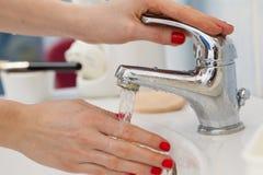 Mãos de lavagem da mulher sob o água da torneira de fluxo no banheiro Imagem de Stock
