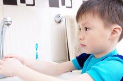 Mãos de lavagem do menino, cuidados médicos pessoais da criança, conceito da higiene, mão de lavagem na bacia de lavagem no banhe Imagem de Stock