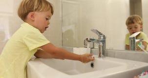 Mãos de lavagem do menino doce perto do espelho