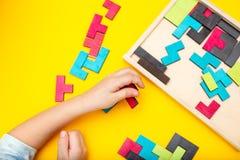 Mãos de madeira do enigma e das crianças no fundo amarelo Configuração lisa foto de stock