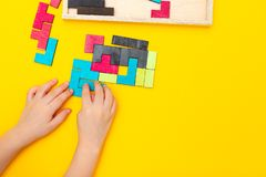 Mãos de madeira do enigma e das crianças no fundo amarelo Copie o espaço foto de stock royalty free