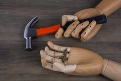 Mãos de madeira que guardam martelos e pregos Imagem de Stock