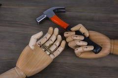 Mãos de madeira que guardam martelos e pregos Fotografia de Stock