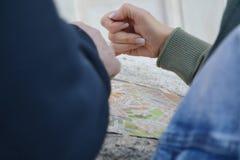 Mãos de Peaple que choicing a maneira no mapa de viagem fotografia de stock royalty free