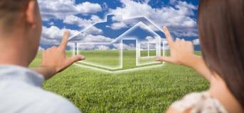 Mãos de quadro dos pares em torno da figura da casa no campo de grama Imagens de Stock Royalty Free