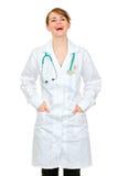 Mãos de riso da terra arrendada da mulher do doutor em uns bolsos Foto de Stock Royalty Free