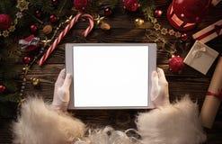 Mãos de Santa Claus que guardam a tabuleta digital vazia fotografia de stock