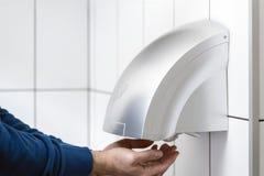 Mãos de secagem do homem usando o secador da mão foto de stock royalty free