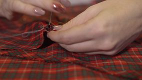 Mãos de um alfaiate novo que costure com uma agulha e uma linha à mão video estoque