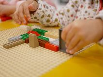 Mãos de um bebê que joga tijolos plásticos de bloqueio coloridos fotografia de stock royalty free