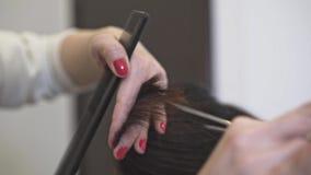 Mãos de um cabeleireiro irreconhecível que corta o cabelo longo escuro de seu cliente video estoque