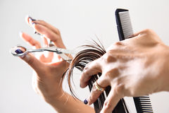 Mãos de um cabelo do aparamento do cabeleireiro com um pente e as tesouras Fotografia de Stock