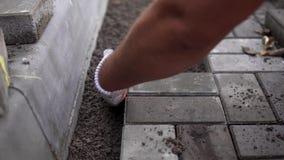 Mãos de um construtor em suas mãos gloved alaranjadas com um encaixe do martelo que coloca as pedras de pavimentação exteriores n video estoque