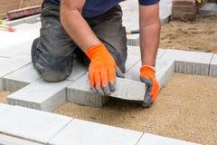 Mãos de um construtor que coloca pedras de pavimentação novas foto de stock