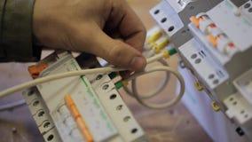 Mãos de um eletricista para conectar o painel de comando a uma fase video estoque