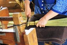 Mãos de um fabricante da vassoura que trabalha em uma vassoura da palha fotos de stock