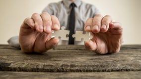 Mãos de um homem de negócios que guarda partes do enigma Imagem de Stock