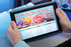 Mãos de um homem em receitas de uma leitura da Web do local para sobremesas Imagens de Stock