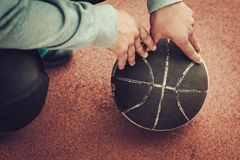 Mãos de um homem em uma bola do basquetebol Imagem de Stock