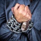 Mãos de um homem formalmente vestido acorrentado com uma corrente do ferro e um a Foto de Stock